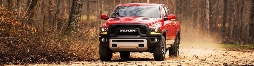 red truck driving down a dirt road